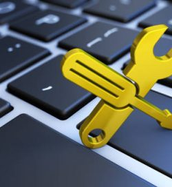 Computer service and assistance concept with a golden work tool icon on a laptop keyboard 3D illustration.